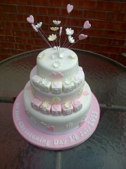 Pink and white christening cake with hearts, flowers, and letter blocks