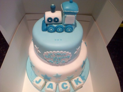 Blue and white train theme christening cake with letter blocks