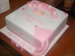 12 inch pink and white christening cake with letter blocks, a baby and a blanket