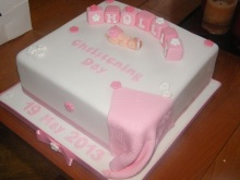 Pink and white christening cake with baby, blanket and letter blocks