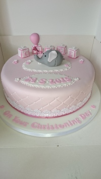 Pink christening cake with letter blocks, cake lace, and an elephant holding a balloon