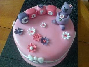 Pink and purple birthday cake with bear and letter blocks