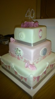Pink and white 40th birthday cake with brooches and bunting