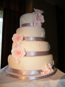 4 tier white wedding cake with pink handmade sugar flowers