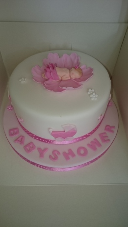 Pink and white baby shower cake with pink lily