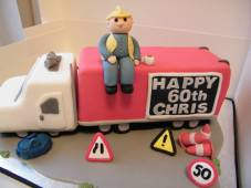 Red and white lorry 60th birthday cake with traffic cones, signs and workman with cup of tea