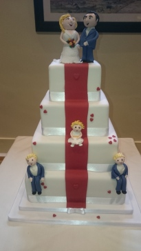 4 tier white wedding cake with red stripe and models of family members