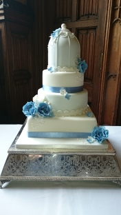 White and blue birdcage wedding cake with handmade sugar flowers