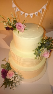 3 tier buttercream wedding cake with fresh roses, foliage and bunting