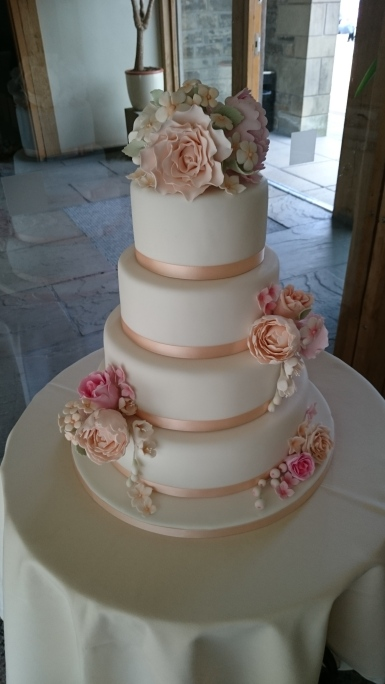 4 tier white wedding cake with peach ribbon and handmade sugar flowers