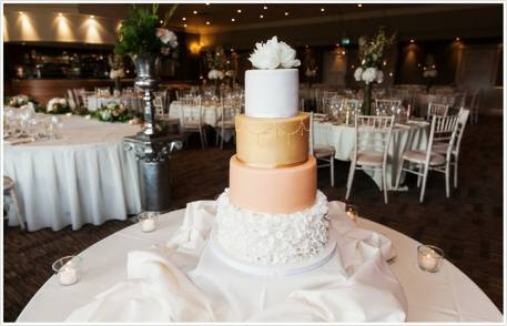 4 tier white, peach and gold wedding cake with ruffles and sugar flowers