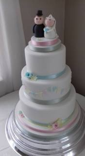 3 tier white wedding cake with bunting, flowers and bride and groom topper