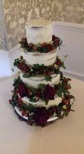 Semi-naked wedding cake with autumn flowers, nuts and leaves