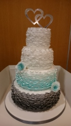 4 tier wedding cake with grey, blue and white graduated ruffles and handmade sugar flowers