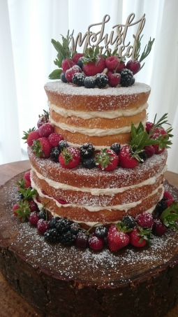 Rustic naked wedding cake with fresh fruit and herbs