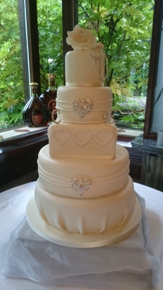 Elegant 5 tier ivory wedding cake with brooches