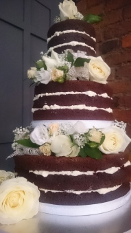Naked chocolate 3 tier wedding cake with fresh flowers