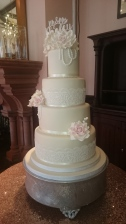 4 tier white wedding cake with pink ribbon, handmade sugar flowers and cake lace