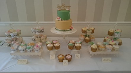 Green and gold wedding cake with cupcakes